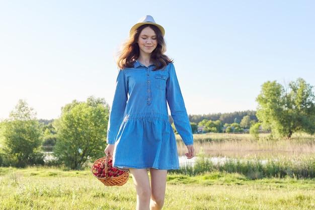 Retrato do país da bela adolescente com chapéu vestido jeans com cesta de morangos frescos. fundo de paisagem natural, prado verde, céu azul