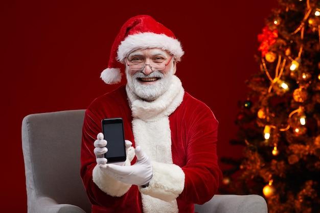 Retrato do papai noel barbudo em óculos, sorrindo, segurando o celular nas mãos