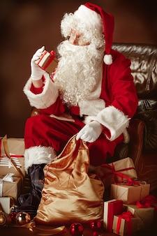 Retrato do papai noel em fantasia vermelha com caixa de presente