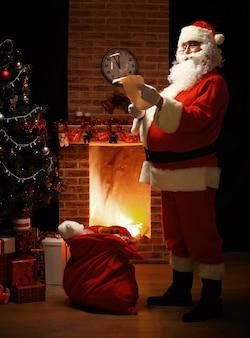 Retrato do papai noel feliz em pé em seu quarto em casa perto da árvore de natal e um grande saco e lendo a carta de natal ou lista de desejos