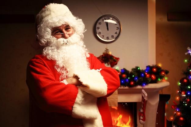 Retrato do papai noel feliz segurando a carta de natal nas mãos e olhando para a câmera