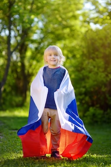 Retrato do parque bonito do verão do rapaz pequeno em público com bandeira do russo. fãs criança apoiando e torcendo sua equipe nacional. dia da independência