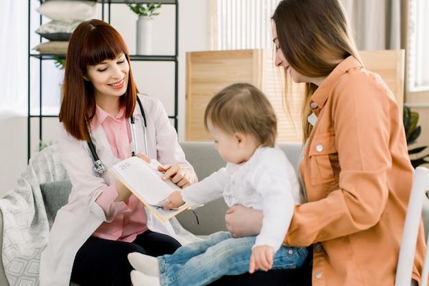 Retrato do pediatra bonito, explicando o tratamento para a jovem mãe e seu bebê, visita do médico em casa