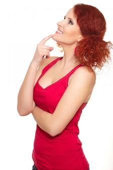 Retrato do pensamento bonito sorrindo ruiva gengibre mulher no pano vermelho em porfile isolado no branco