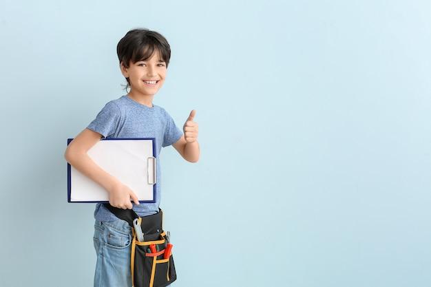 Retrato do pequeno encanador mostrando gesto do polegar para cima na cor de fundo