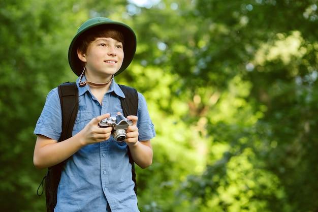 Retrato do pequeno explorador com câmera fotográfica na floresta