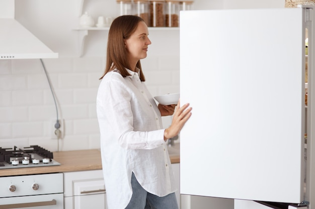 Retrato do perfil da bela jovem adulta vestindo camisa branca, olhando sorrindo dentro da geladeira com um sorriso agradável, segurando o prato nas mãos, posando com cozinha em segundo plano.
