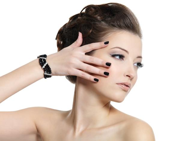 Retrato do perfil da linda garota glamour com unhas pretas isoladas no branco