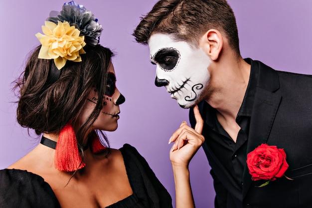 Retrato do perfil da menina com acessórios coloridos brilhantes e o homem de jaqueta preta com rosa no bolso, olhando um para o outro.