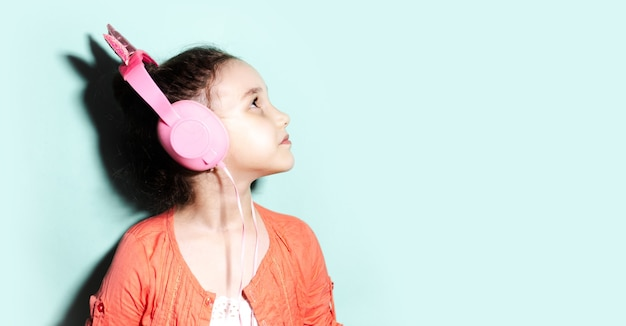 Retrato do perfil da menina criança olhando para cima, usando fones de ouvido, vestindo a camisa rosa coral no fundo do estúdio do aqua menta cor com espaço de cópia.