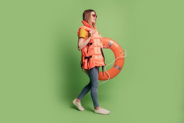 Retrato do perfil da senhora caminhar no espaço vazio segurar um círculo inflável usar calça jeans colete laranja sobre fundo verde