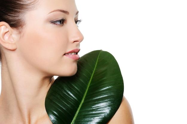 Retrato do perfil de saúde de uma jovem bonita e bonita com folhas verdes