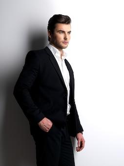 Retrato do perfil de um jovem fashion de terno preto posando no estúdio