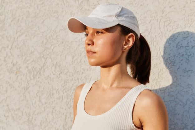 Retrato do perfil de uma garota séria e pensativa, usando blusa e boné branco, olhando para longe