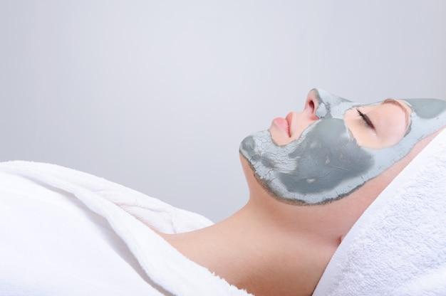 Retrato do perfil de uma jovem com máscara de argila no rosto