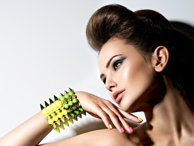 Retrato do perfil de uma linda mulher usando pulseira com espinhos e unhas multicoloridas