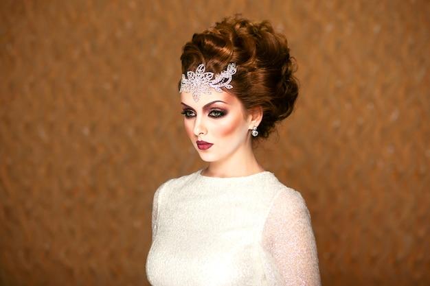 Retrato do perfil de uma linda noiva, com maquiagem e penteado em fundo marrom