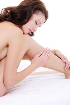 Retrato do perfil de uma mulher nua sexy tocando suas belas pernas longas, sentada na cama
