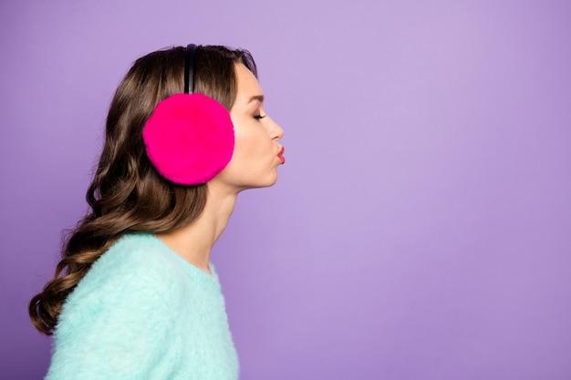 Retrato do perfil do close up da senhora encaracolada atraente enviando beijos do ar do espaço vazio olhos fechados do encontro às cegas usar protetores de ouvido quentes rosa fuzzy pastel macio pulôver.