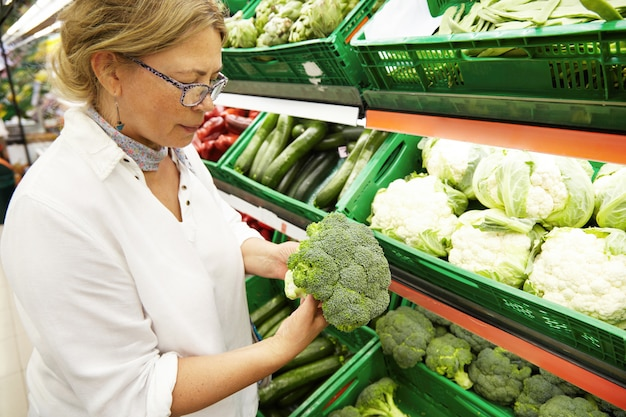 Retrato do perfil do close-up do vegetariano caucasiano de meia idade bonito da mulher na roupa ocasional que escolhe e que escolhe os vegetais e os brócolis os mais frescos na mercearia. pessoas e compras