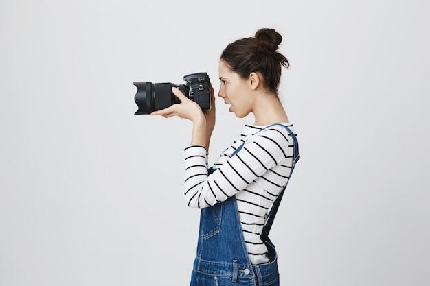 Retrato do perfil do fotógrafo de uma garota bonita olhando pelas lentes da câmera, tirando fotos