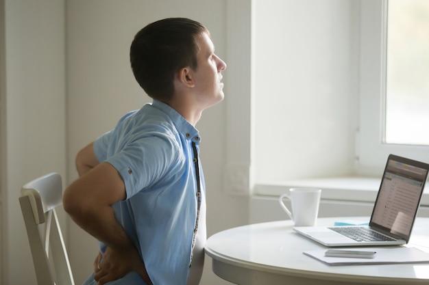 Retrato do perfil do homem no laptop, alongamento, posição dor nas costas