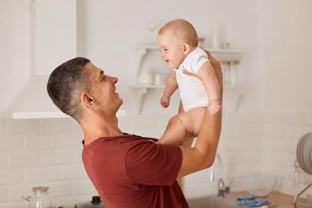 Retrato do perfil do homem vomitando a filhinha infantil, passando o tempo com o bebê, posando em uma sala iluminada com cozinha situada no fundo, paternidade feliz.