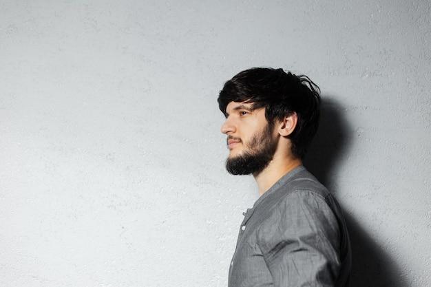 Retrato do perfil do jovem sério barbudo com cinza.
