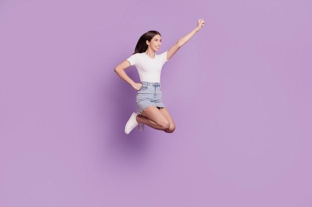 Retrato do perfil do super-herói bonito, senhora simpática, pular, levantar mão, voar, salvar o mundo, sobre fundo roxo