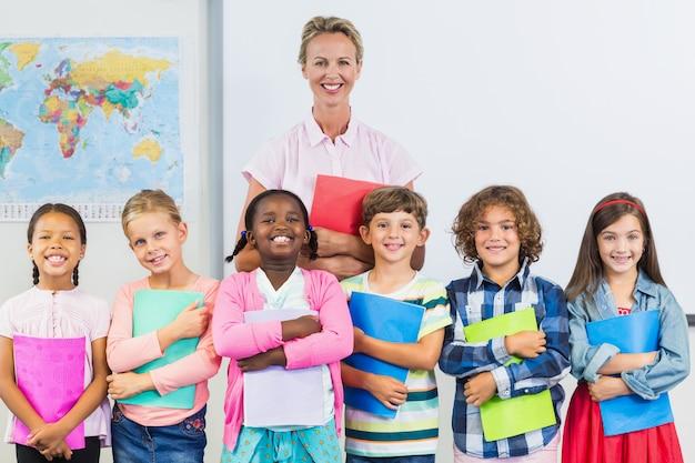 Retrato do professor sorridente e crianças em pé na sala de aula