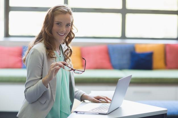 Retrato do professor sorridente usando o laptop na biblioteca