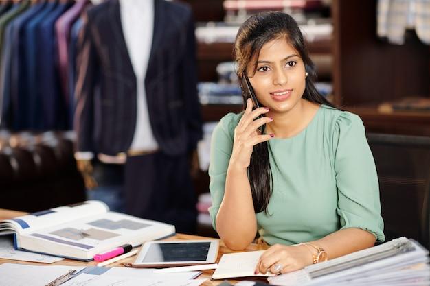 Retrato do proprietário de um ateliê indiano muito jovem e adorável falando ao telefone com o cliente sentado à mesa com catálogos e planejador