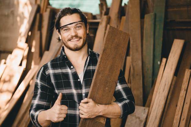 Retrato do proprietário de uma loja de móveis de pme jovem carpinteiro sorrindo em uma oficina de madeira parece um artesão profissional qualificado de pessoas reais.