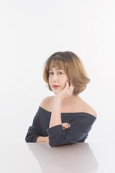 Retrato do queixo asiático do suporte da mulher na mesa isolada na reflexão branca, copyspace de forma livre. esta imagem para a pele da beleza.