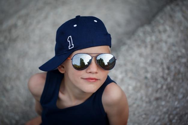 Retrato do rapaz pequeno elegante nos óculos de sol e no tampão. infância. horário de verão.