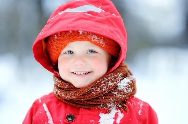 Retrato do rapaz pequeno feliz na roupa vermelha do inverno que tem o divertimento durante a queda de neve. lazer ativo ao ar livre com crianças no inverno