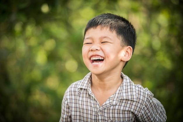 Retrato do rapaz pequeno feliz que ri quando jogar no parque.
