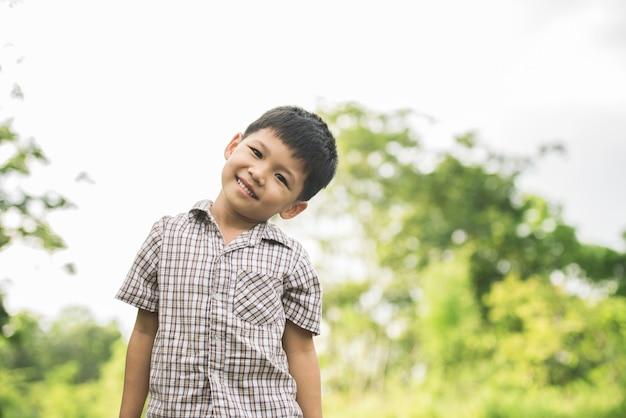 Retrato do rapaz pequeno que está no parque natural que sorri à câmera.