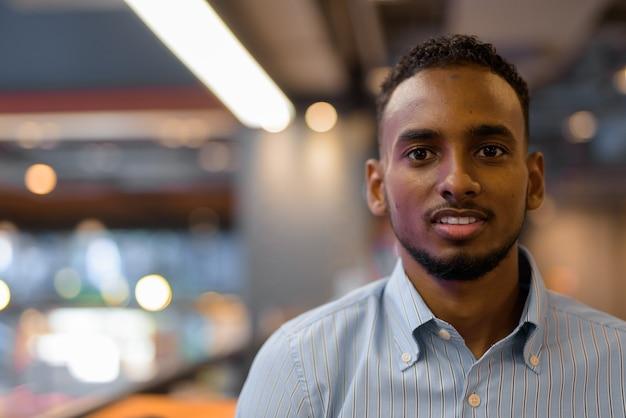 Retrato do rosto bonito de um empresário negro africano olhando para a câmera dentro de um shopping center