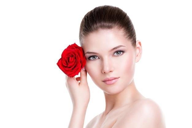 Retrato do rosto bonito de uma mulher bonita com uma rosa vermelha - isolada no branco.