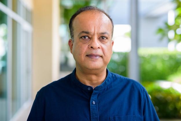 Retrato do rosto de um homem indiano ao ar livre olhando para a câmera