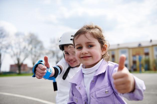 Retrato do rosto de um menino adorável com capacete de skate e uma menina sentada perto da outra e mostrando o polegar