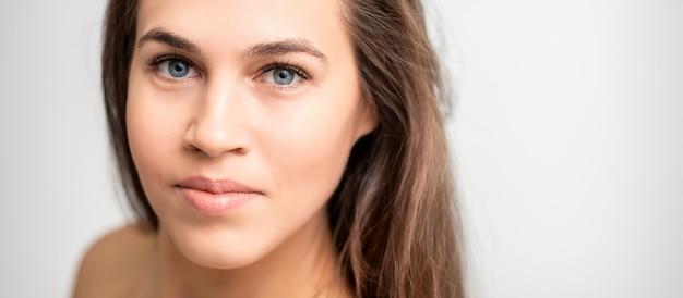 Retrato do rosto de uma jovem mulher branca com maquiagem natural e extensões de cílios na parede branca