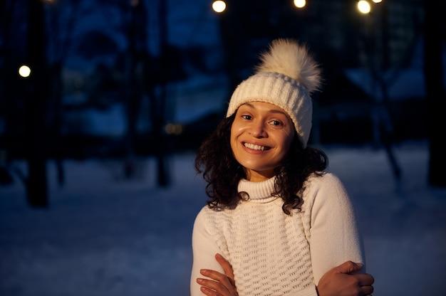 Retrato do rosto de uma mulher sorridente com um chapéu de lã branco no fundo coberto de neve