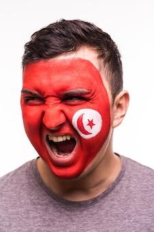 Retrato do rosto do torcedor feliz apoiando a seleção da tunísia com o rosto pintado isolado no fundo branco