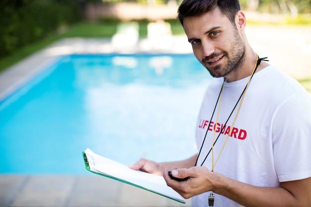 Retrato do salva-vidas segurando a prancheta e o cronômetro à beira da piscina em um dia ensolarado