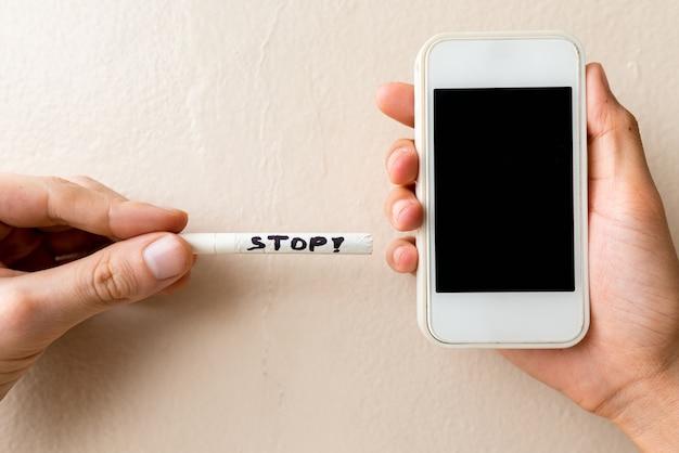 Retrato do sinal de stop escrito no cigarro e no telefone
