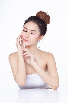 Retrato do sorriso asiático de assento da mulher atrativa no fundo branco.
