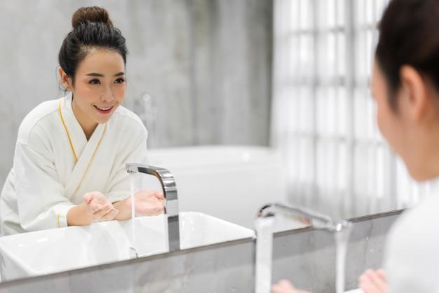 Retrato do sorriso da mulher asiática bonita alegre bonita pele branca saudável fresca limpa, lavar o rosto limpo com água na frente do espelho no banheiro. beleza e spa. pele fresca perfeita