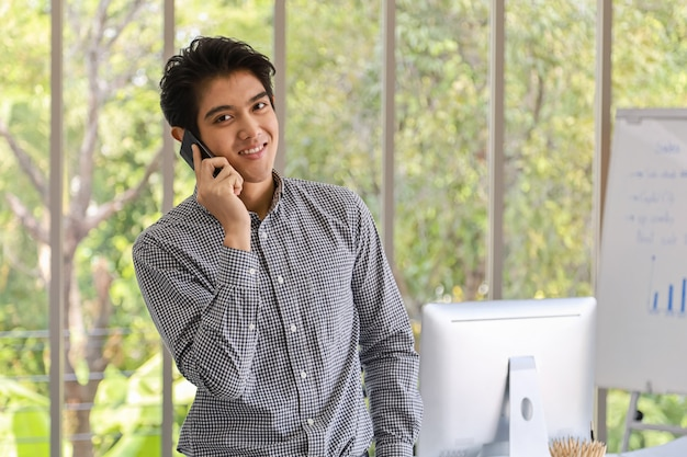 Retrato do sorriso inteligente jovem empresário asiático fazer uma ligação e se sentir feliz com o telefone móvel esperto